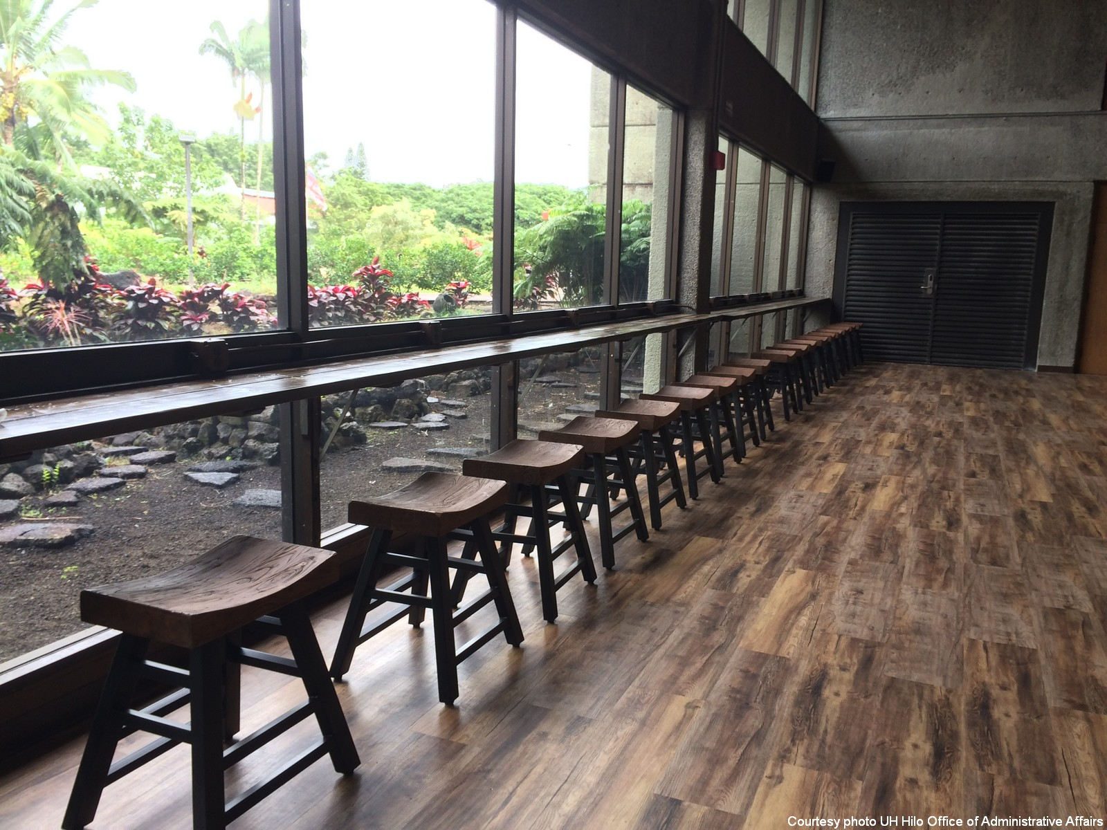 Rustic stools lined up at new rustic counter overlooking gardens.