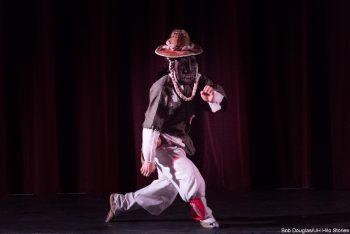 Masked performer, dancing.