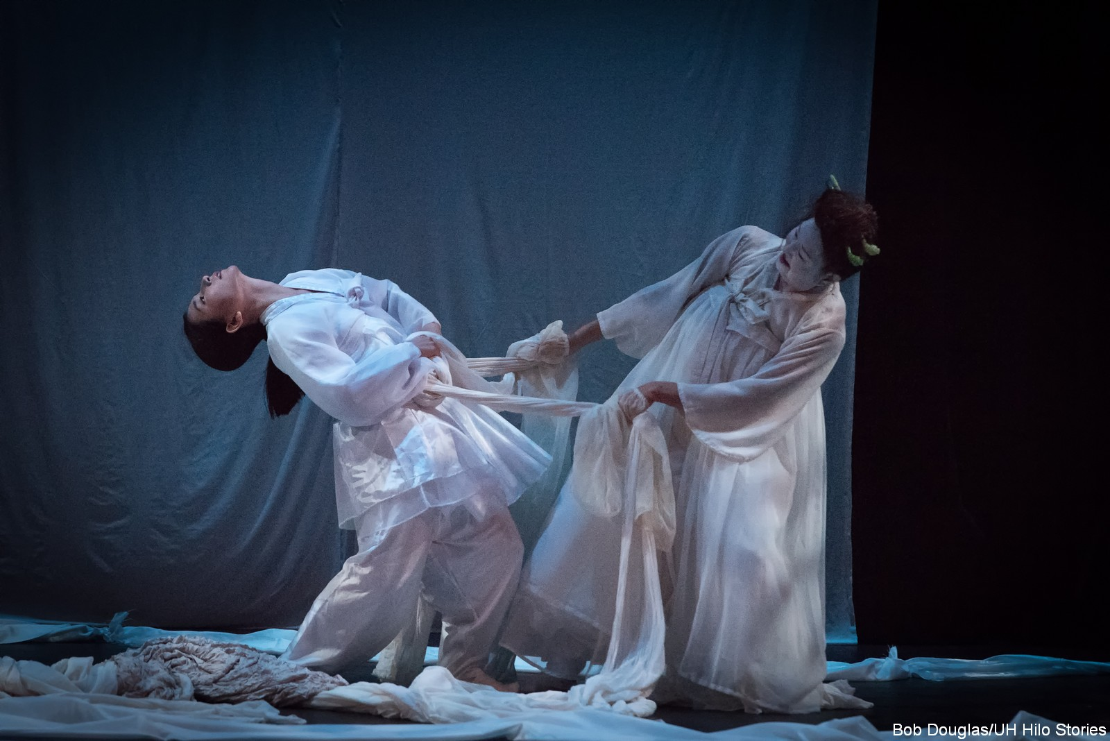 Two women in white performing, pulling at a long white piece of fabric.