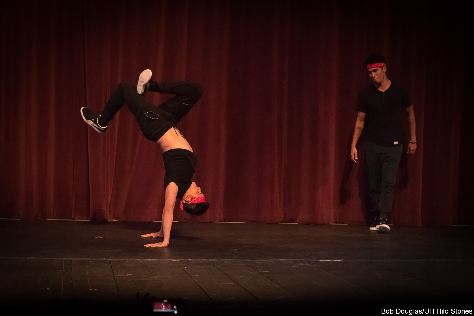 Dancer in modern black costume, doing handstand.