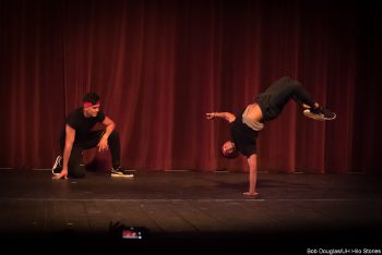 Dancer in modern black costume, spinning handstand