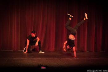 Dancer in modern black costume, spinning handstand.