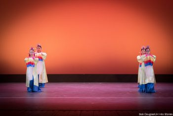 Dancers in red, blue, cream costumes, standing
