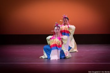 Dancers in red, blue, cream costumes, kneeling.