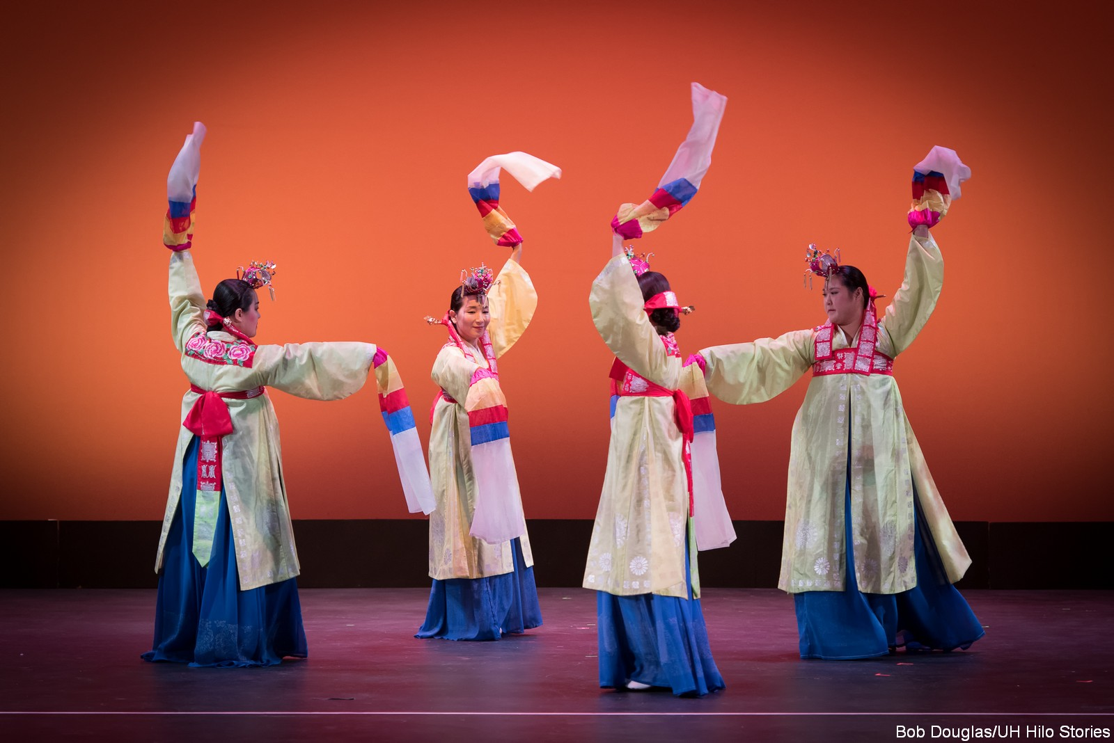 Dancers in red, blue, cream costumes, waving scarves.