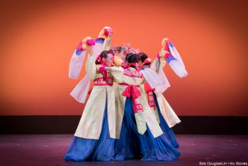 Dancers in red, blue, cream costumes, huddled, waving scarves.