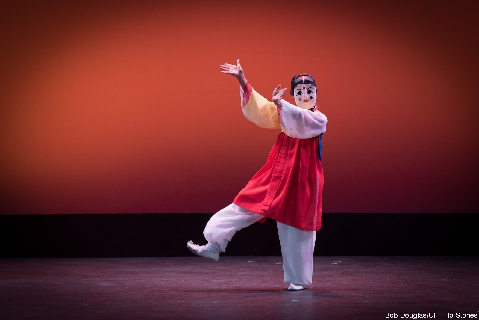 Masked dancer in white pants, red dress, hands extended.