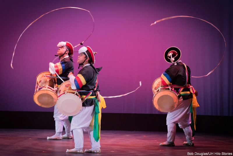 Three men dancing with ribbons and drums.