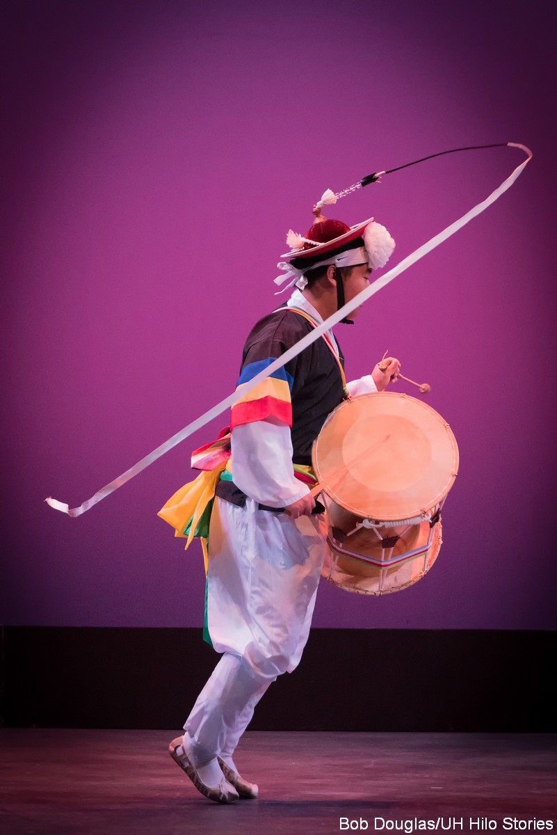 Man dancing, holding drum, ribbon spinning from hat on his head.