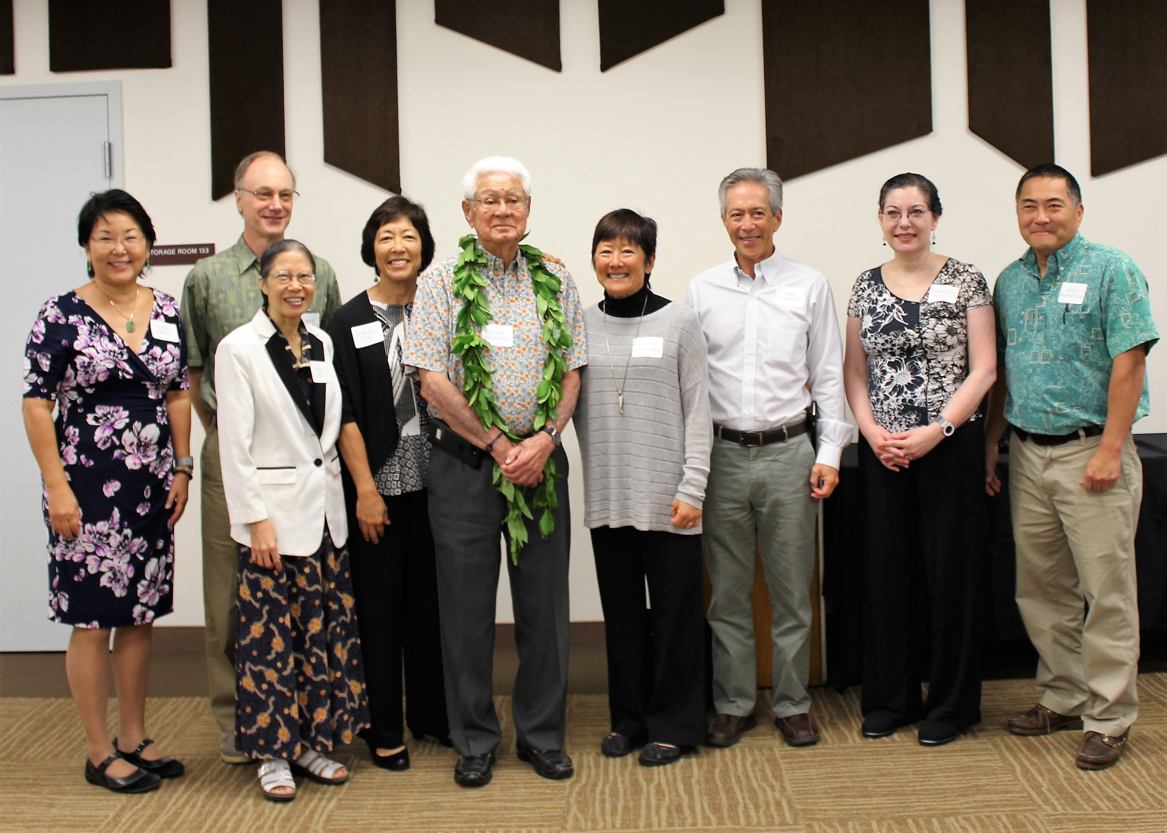 Group standing for photo. Benefactor Bobby Fujimoto wears a lei.
