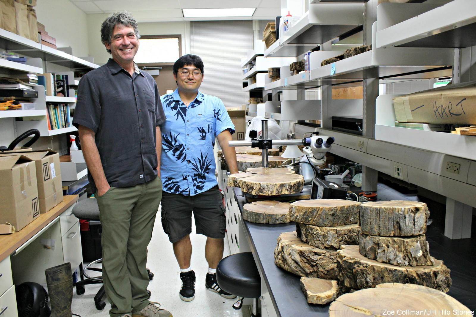 Prof. Hart and grad student Shea Uehana standing in aisle in lab. Wood samples are stacked on the shelf.