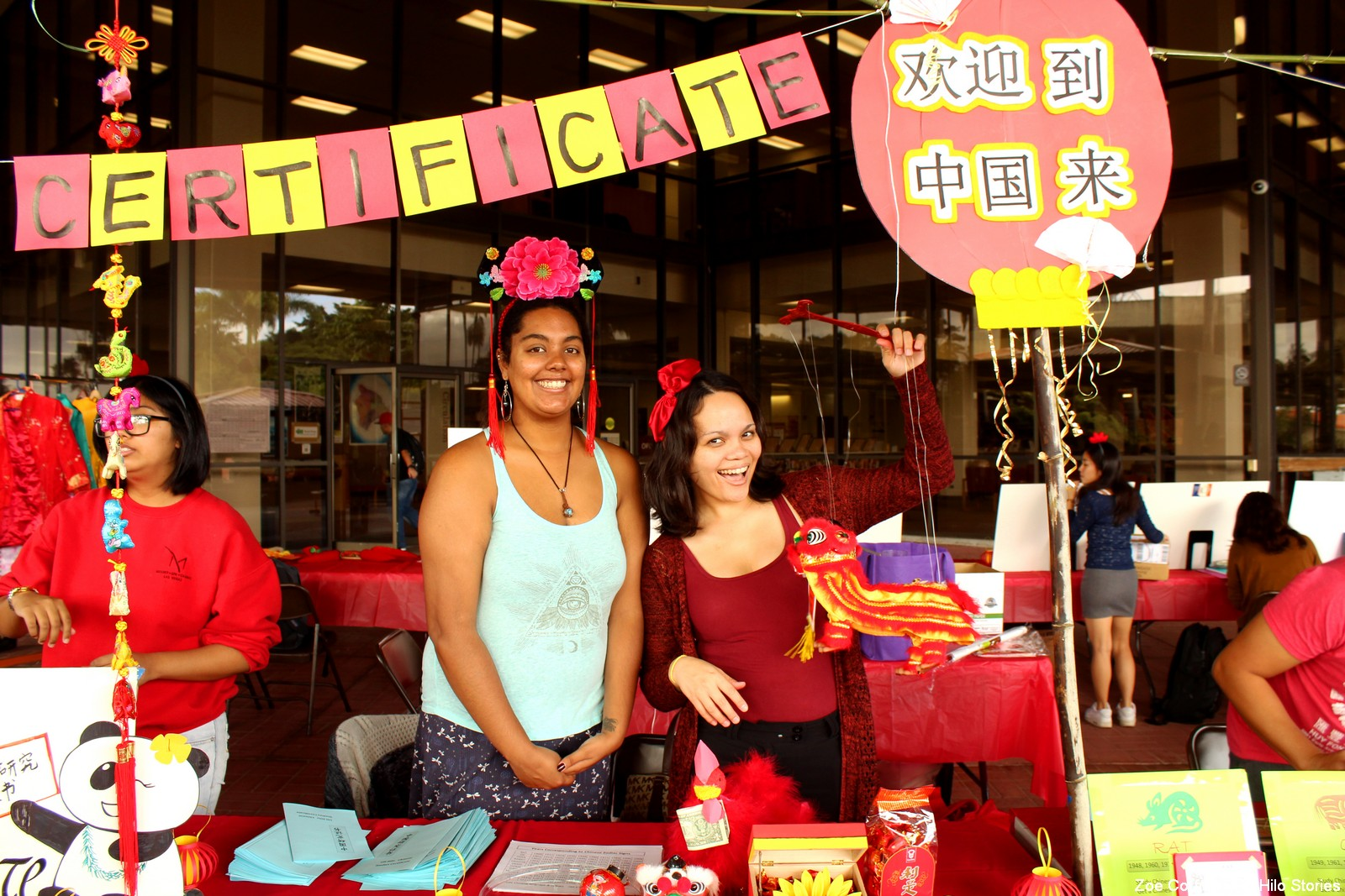 Two students at a booth, very colorful with Chinese decorations, calligraphy, banner.