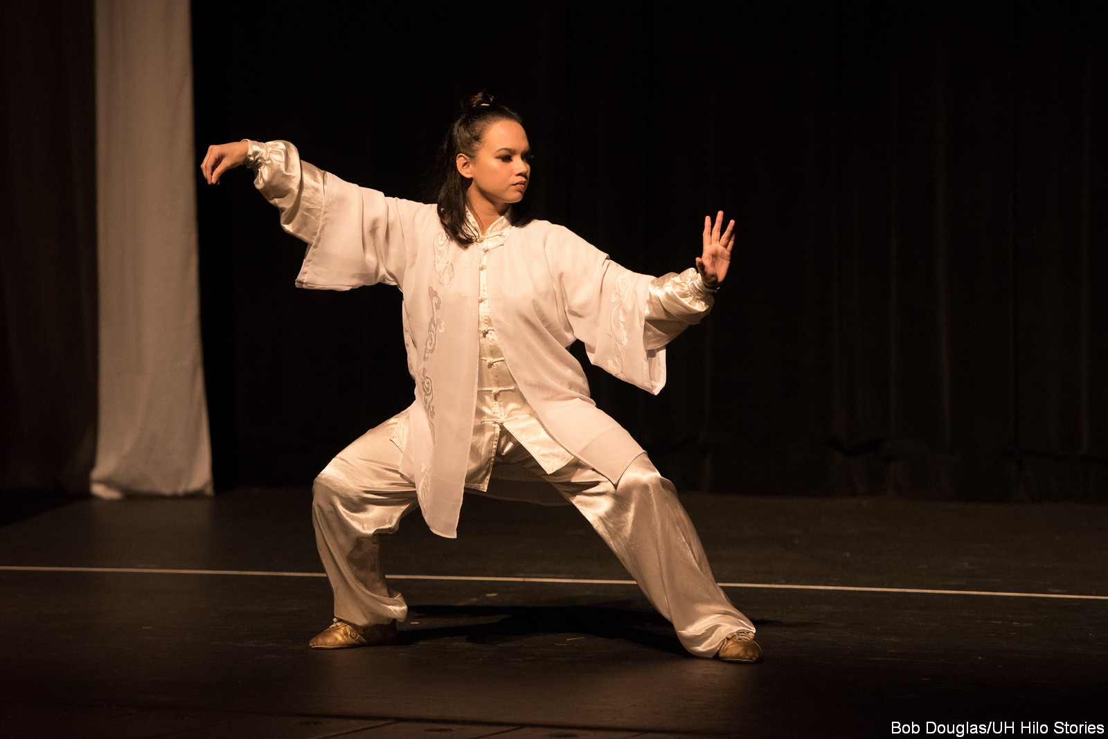 Dancing in off white costume, tai chi poses.