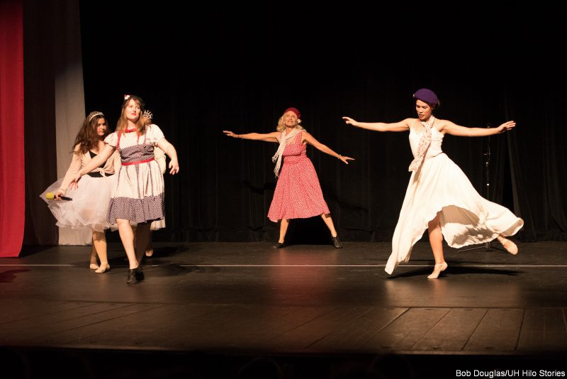 Dancers in white gauzy material, wearing berets and ballet slippers.