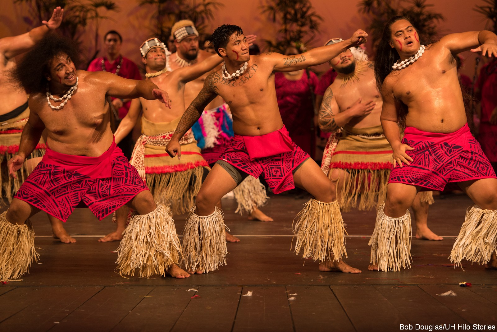 Male dancers with red costume, gesturing up, shell lei, grass fringe on legs, some in headdress.