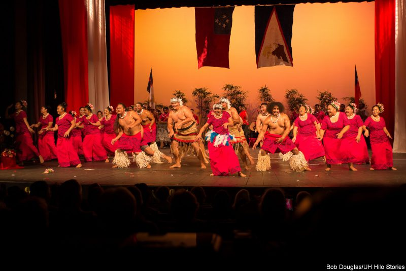 Male and female dancers with red costume, gesturing up, shell lei, grass fringe on legs, some in headdress.