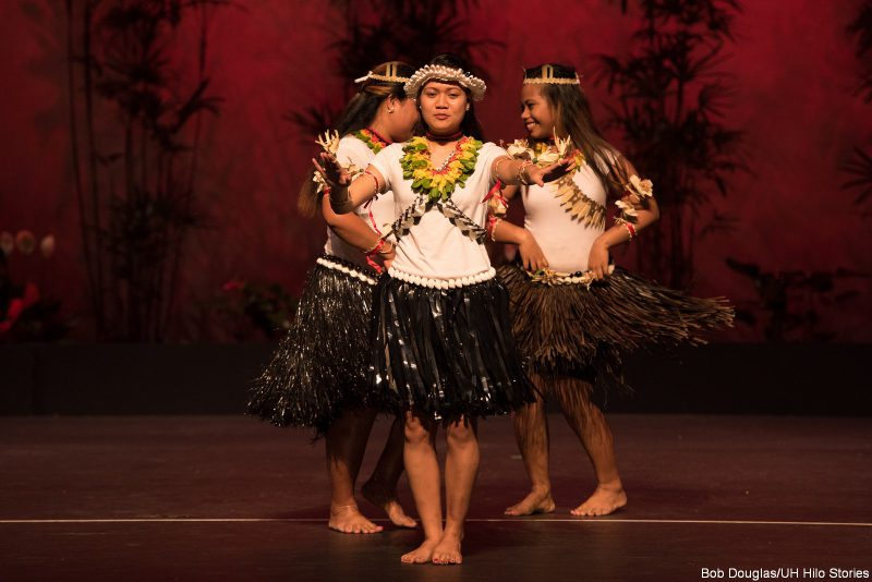 Young women dancing in white tops and brown fringey skirts, lei.