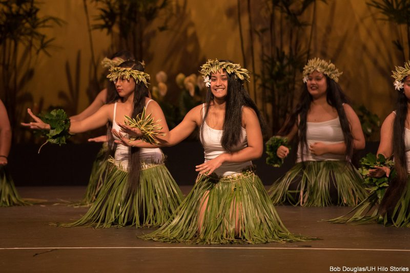 Kosrae dancers in white top and green skirt made of leaves.