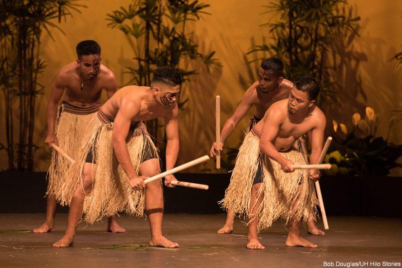Male dancers beating sticks.