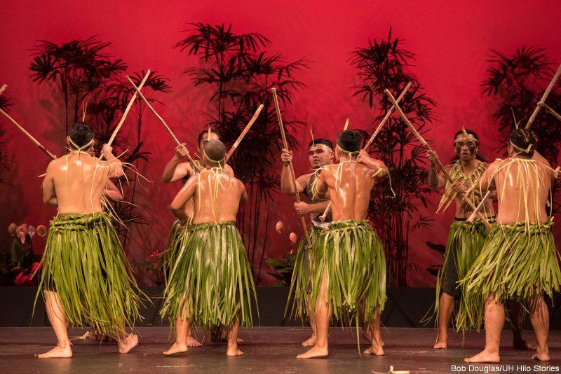 Male dancers in leaf skirts holding long sticks.