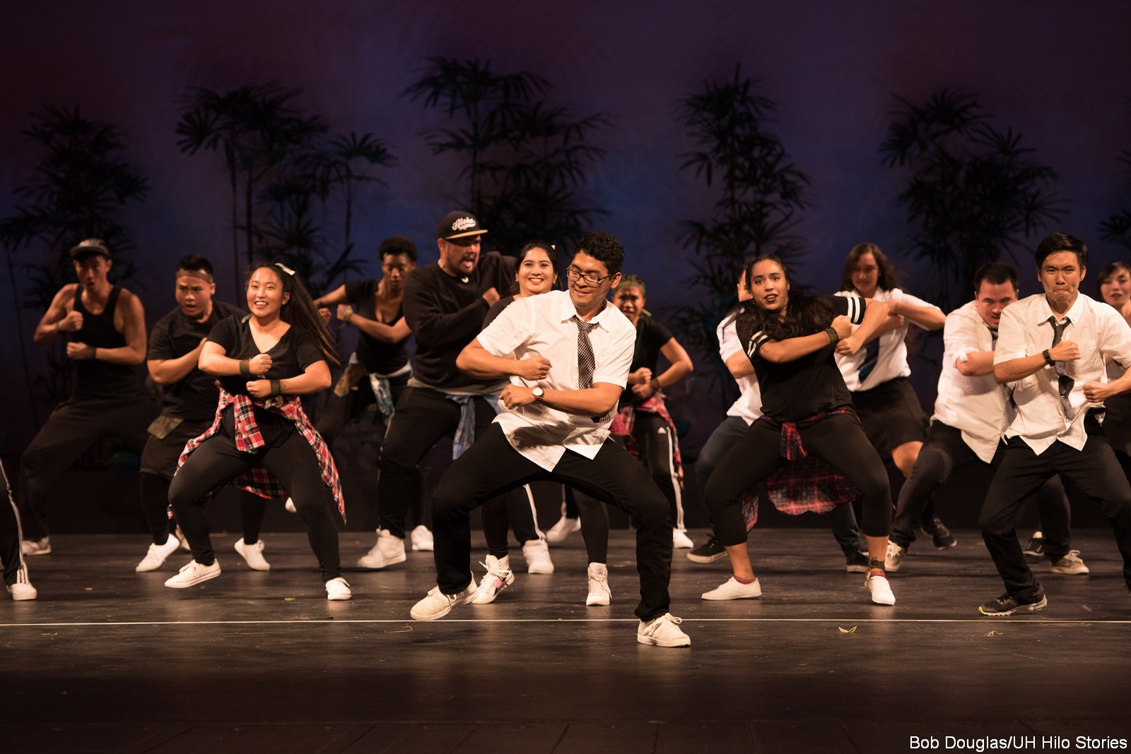 Large group of men and women dancing in modern black and white garb, white shoes.