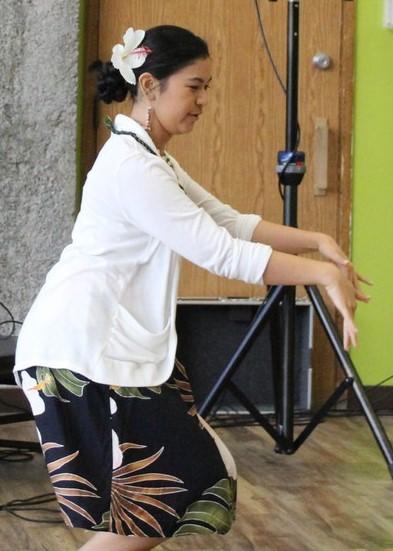 Female performer dances hula.
