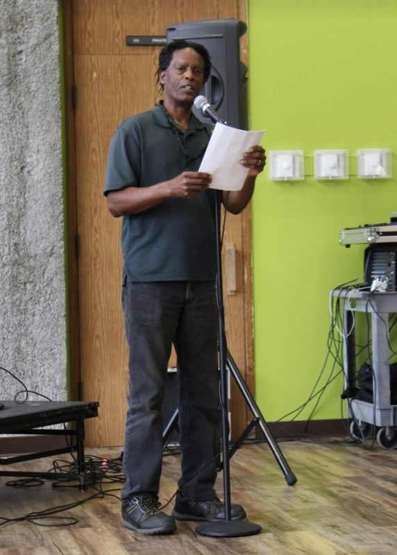 Male performer reads at microphone.