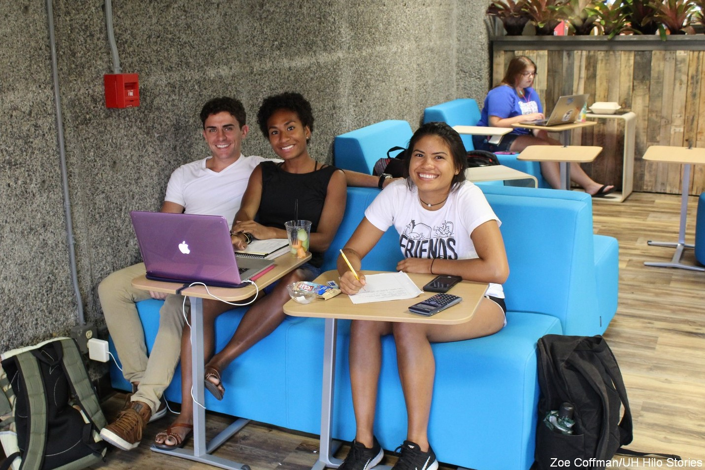 Three students seated on the new bright blue furniture.