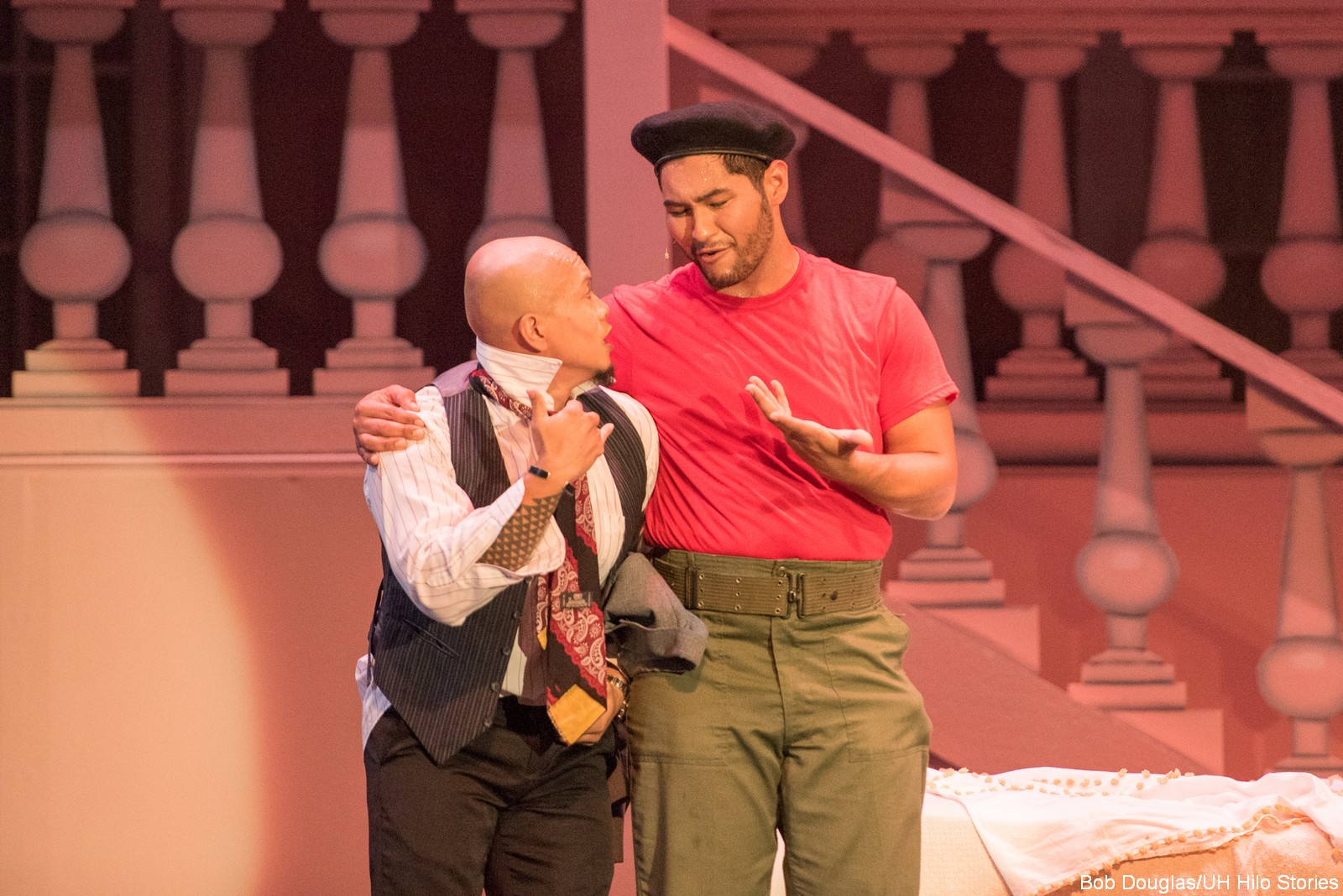 Two actors on stage conversing.