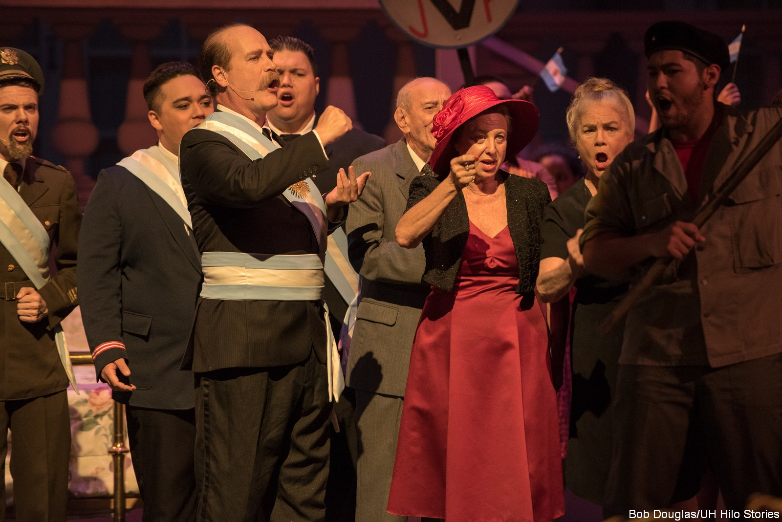 Group singing, woman in red hat.