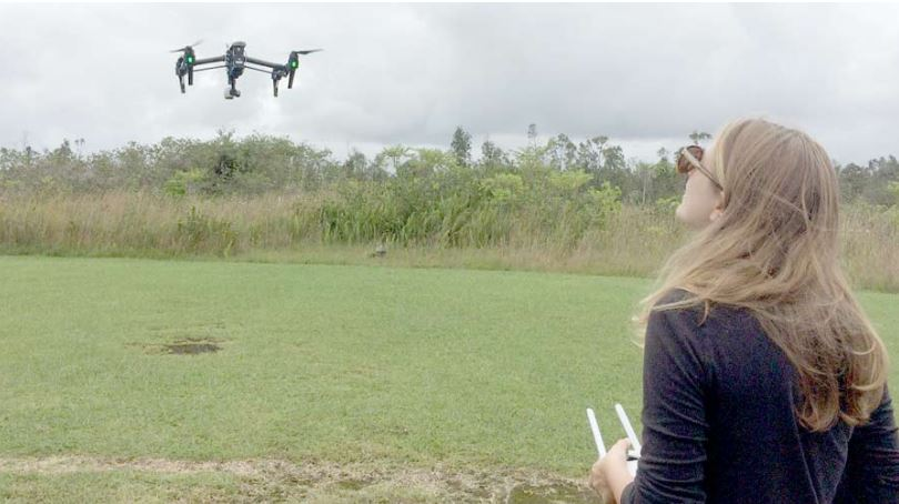 Rose Hart guides an unmanned aerial vehicle in an open field.