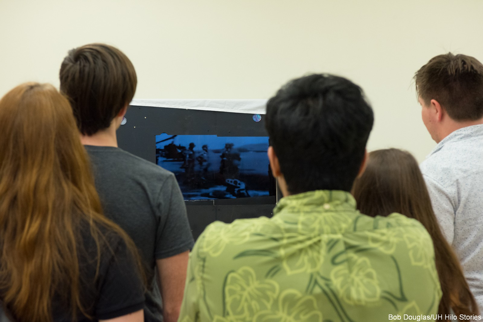 Group of students watch a television screen.