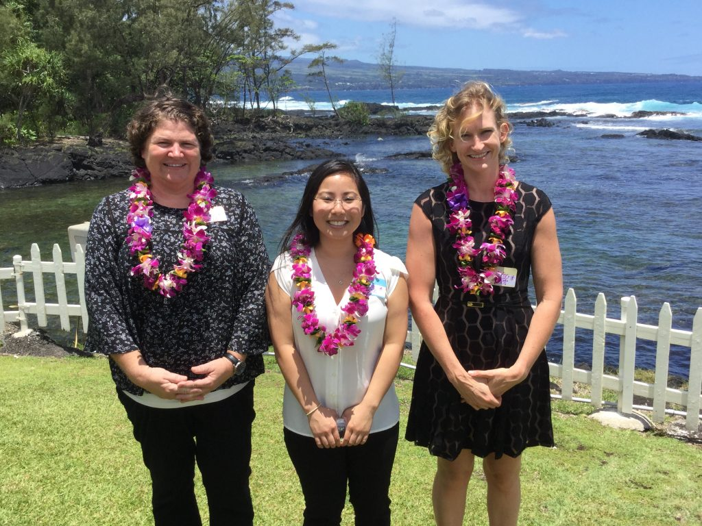 Nicole Garcia, Heather Ah Cook, and Katherine S. Post standing with lei, ocean in background.