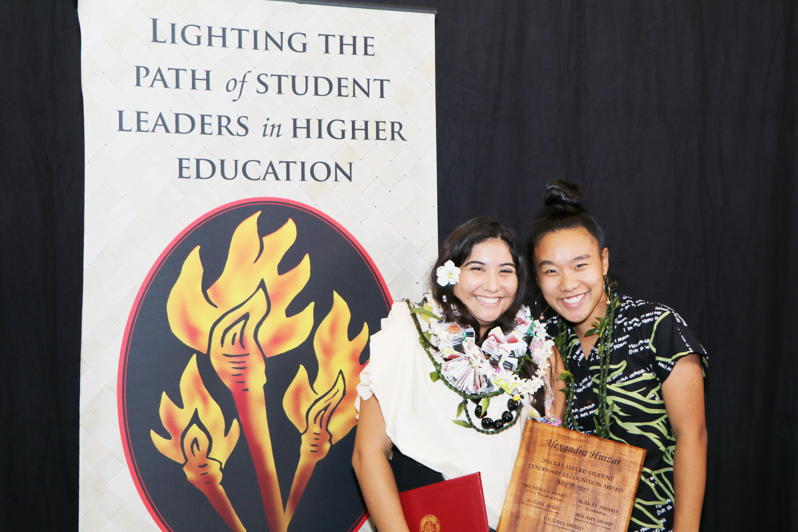 Alexandra Huizar & Megan Escalona standing in front of logo with torches