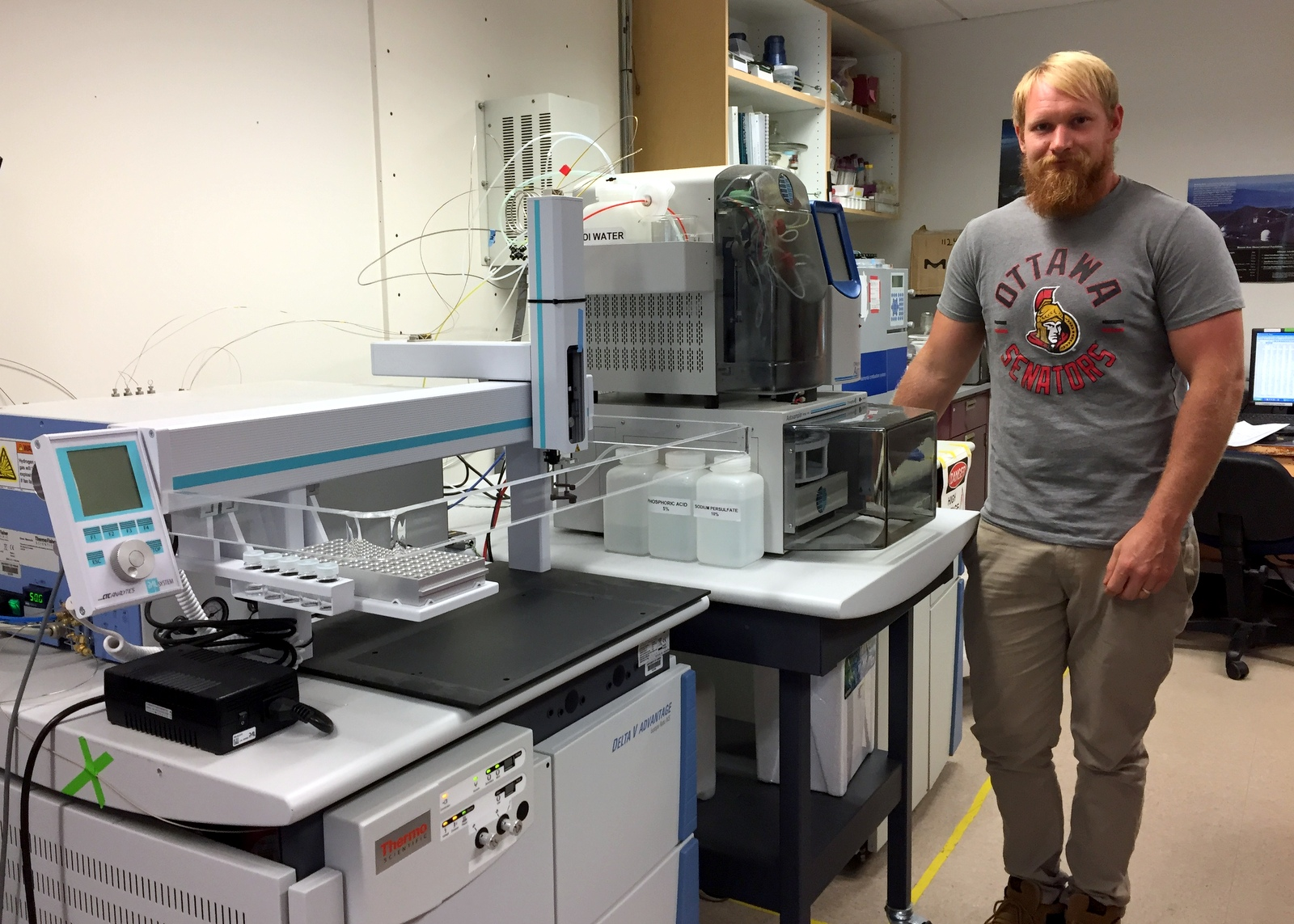 Erik Johnson stands next to the spectrometer.