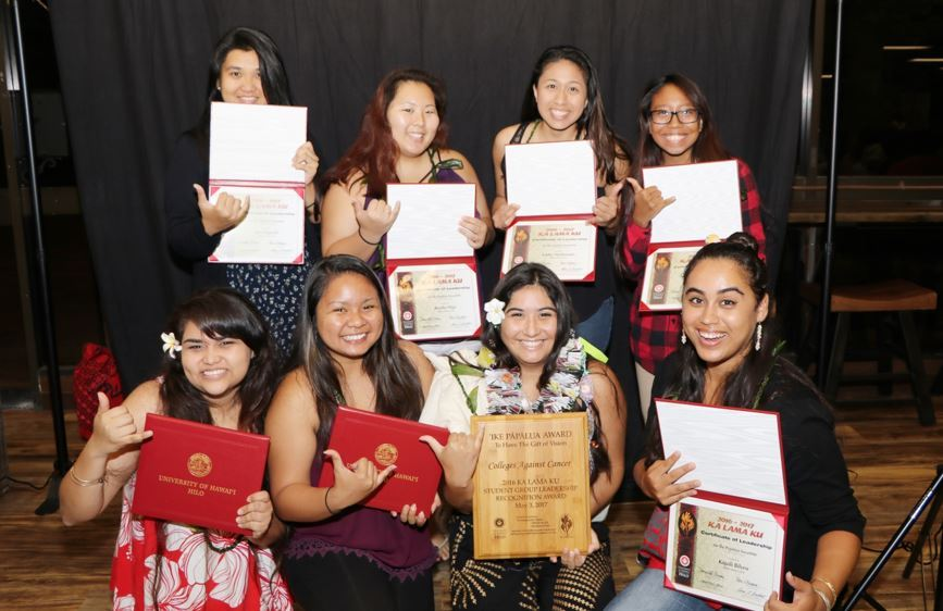 Photo of group, each person holding up certificates they just received.