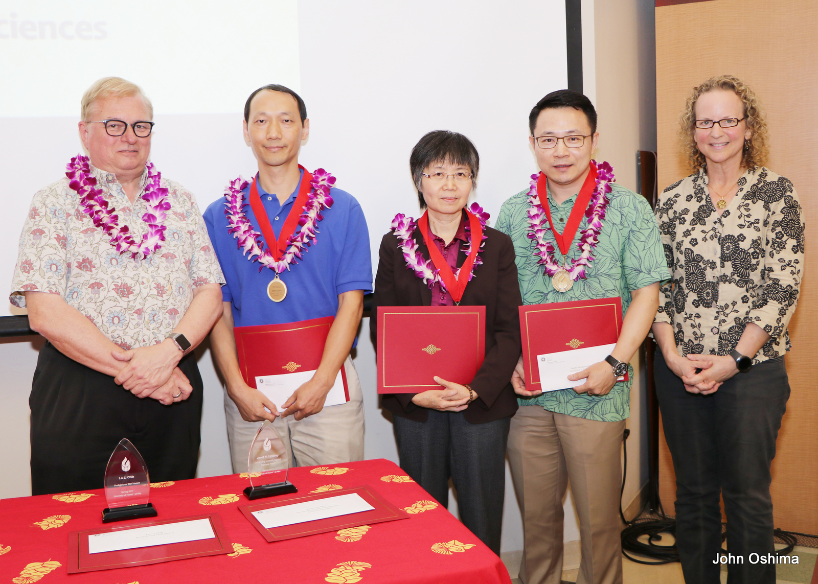 Group stands together, chancellor and recipients have lei and each recipient holds certificate.