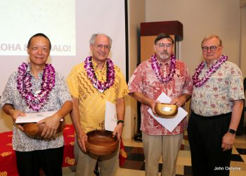 Three retirees who attended the event stand with the chancellor. All have lei. Recipients also hold koa bowls.