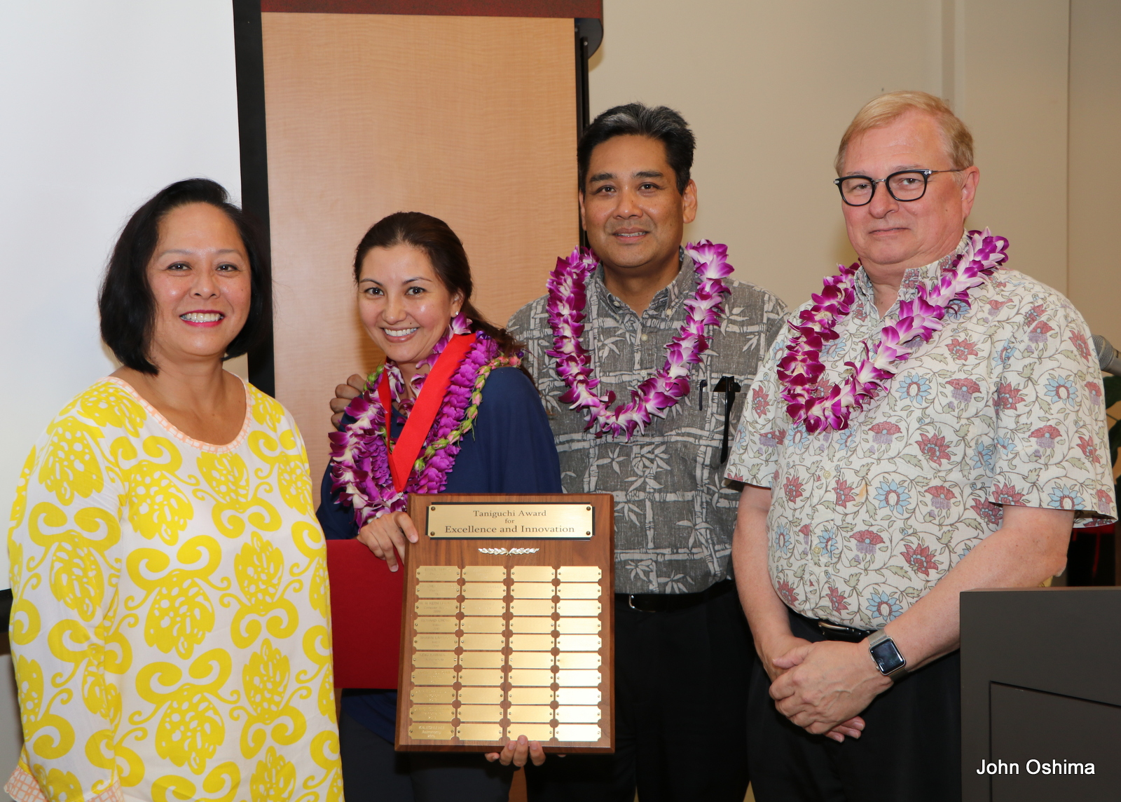 Group stand together, award recipient, donor and chancellor with lei. Lara Gomez hold large plaque.