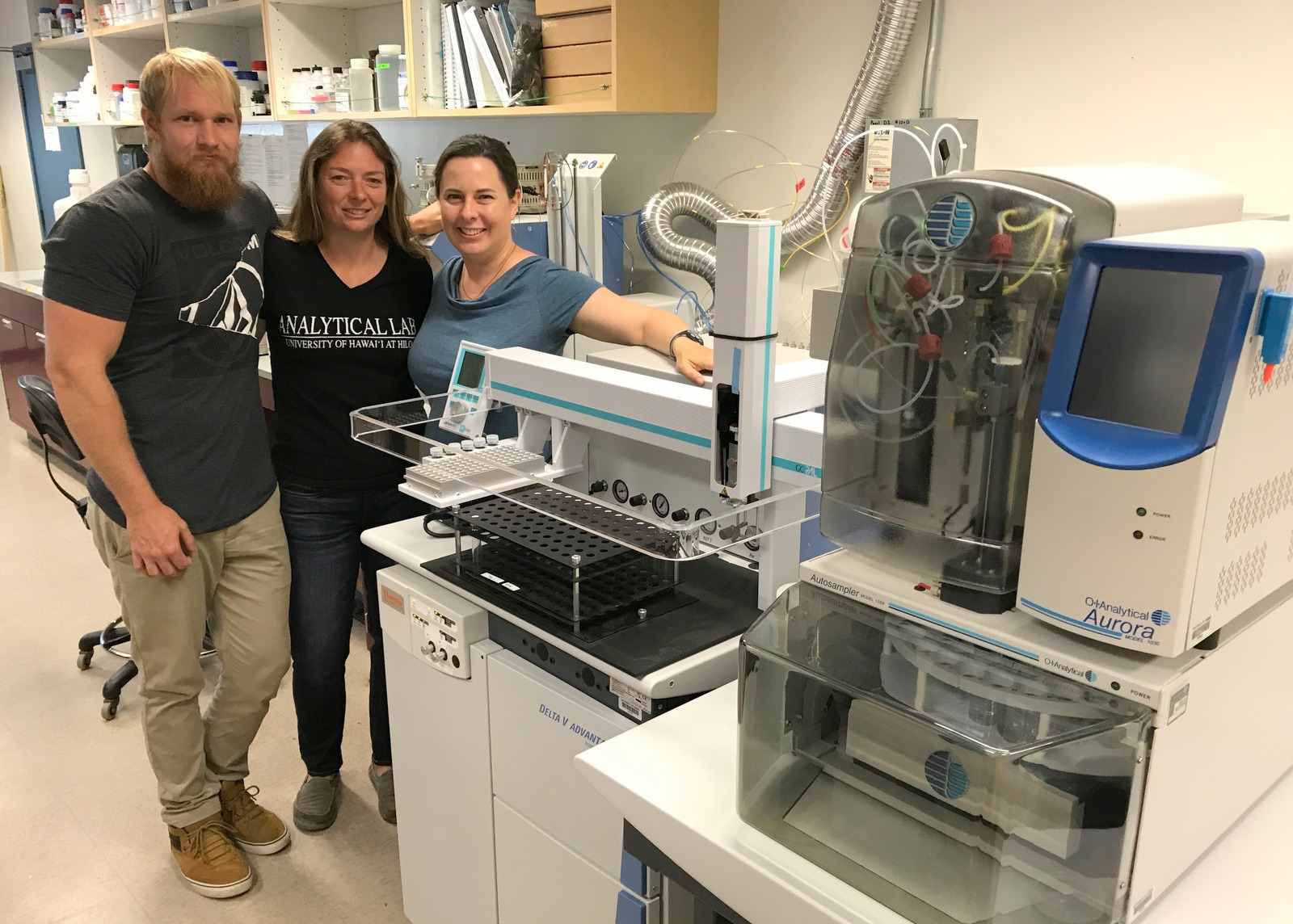 Technician Erik Johnson, Lab Manager Tara Holitzki and Prof. of Marine Science Tracy Wiegner stand next to the new Isotope Ratio Mass Spectrometer, UH Hilo Analytical Labratory.