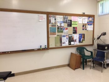 Old classroom arrangement with one small whiteboard behind instructor's desk.