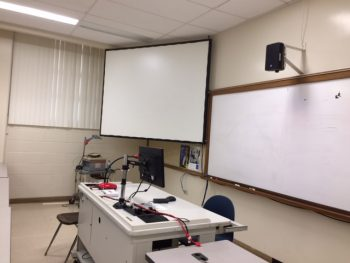 Old classroom arrangement of faculty desk at front of classroom and one large screen in corner.