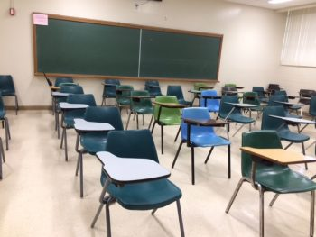Old classroom with standard lines of desks and connected chairs all faced forward.