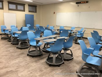 Large white board. Desks and chairs arranged in groupings to allow student to interact.