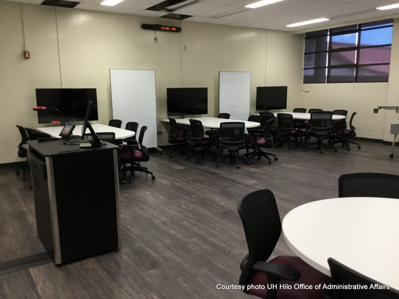Podium at left. Chairs and desks are grouped so 6-8 students each have their own large high definition screen with large table for discussion, laptops and writing.