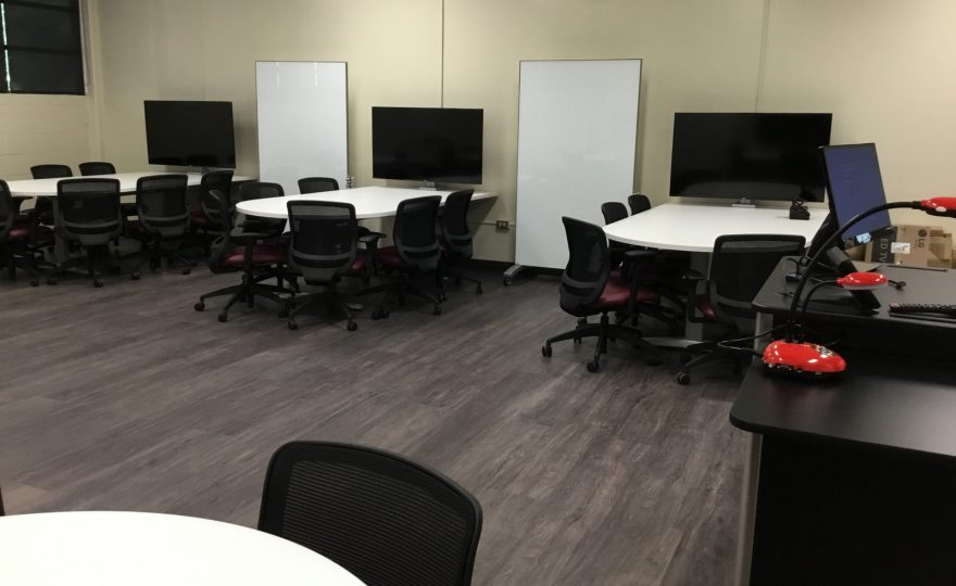 Chairs and desks are grouped so 6-8 students each have their own large high definition screen with large table for discussion, laptops and writing.