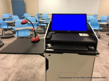 Main lectern with screen and control panel. Desks and chairs for students in background.