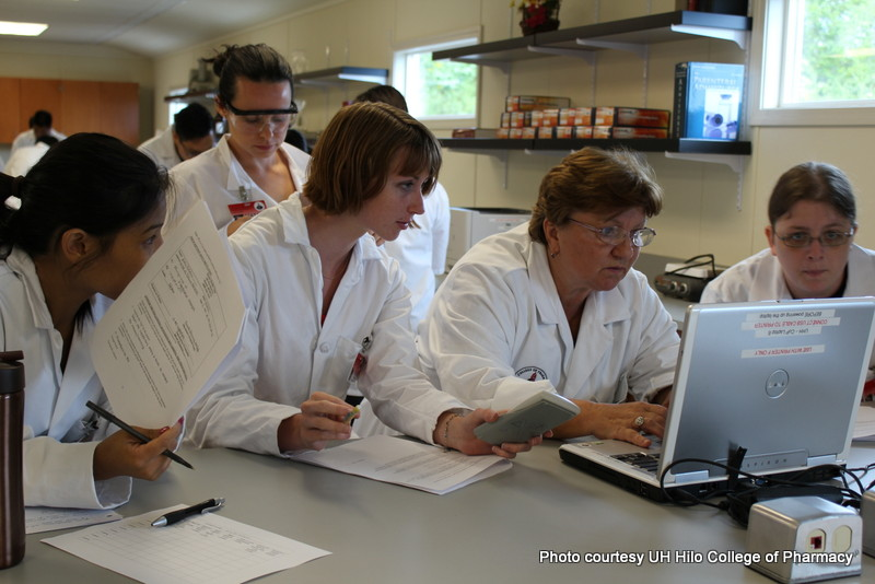 Female students with female faculty working together in lab.