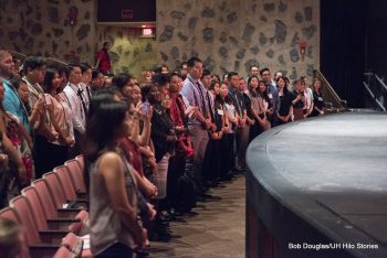 Students standing at their seats in theater., facing dais., can see the edge of the stage.