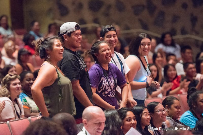 A group of five students stand at their seats surrounded by a full house at the Performing Arts Center.